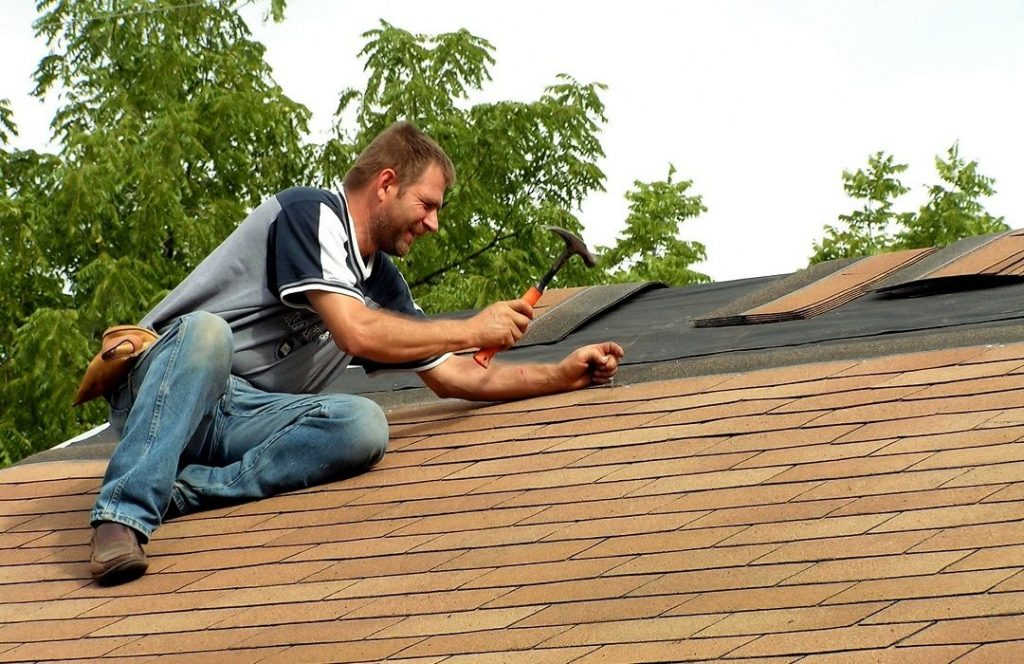 Man Hammering Nail on Roof